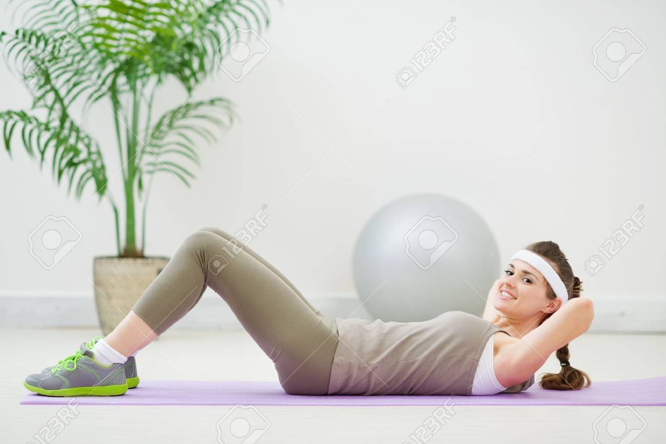Happy slim woman doing abdominal crunch Stock Photo - 13743413