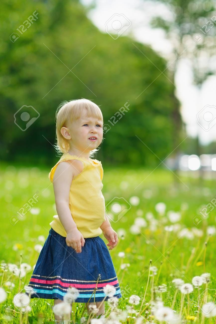 Baby girl on dandelions field looking on copy space Stock Photo - 14003156