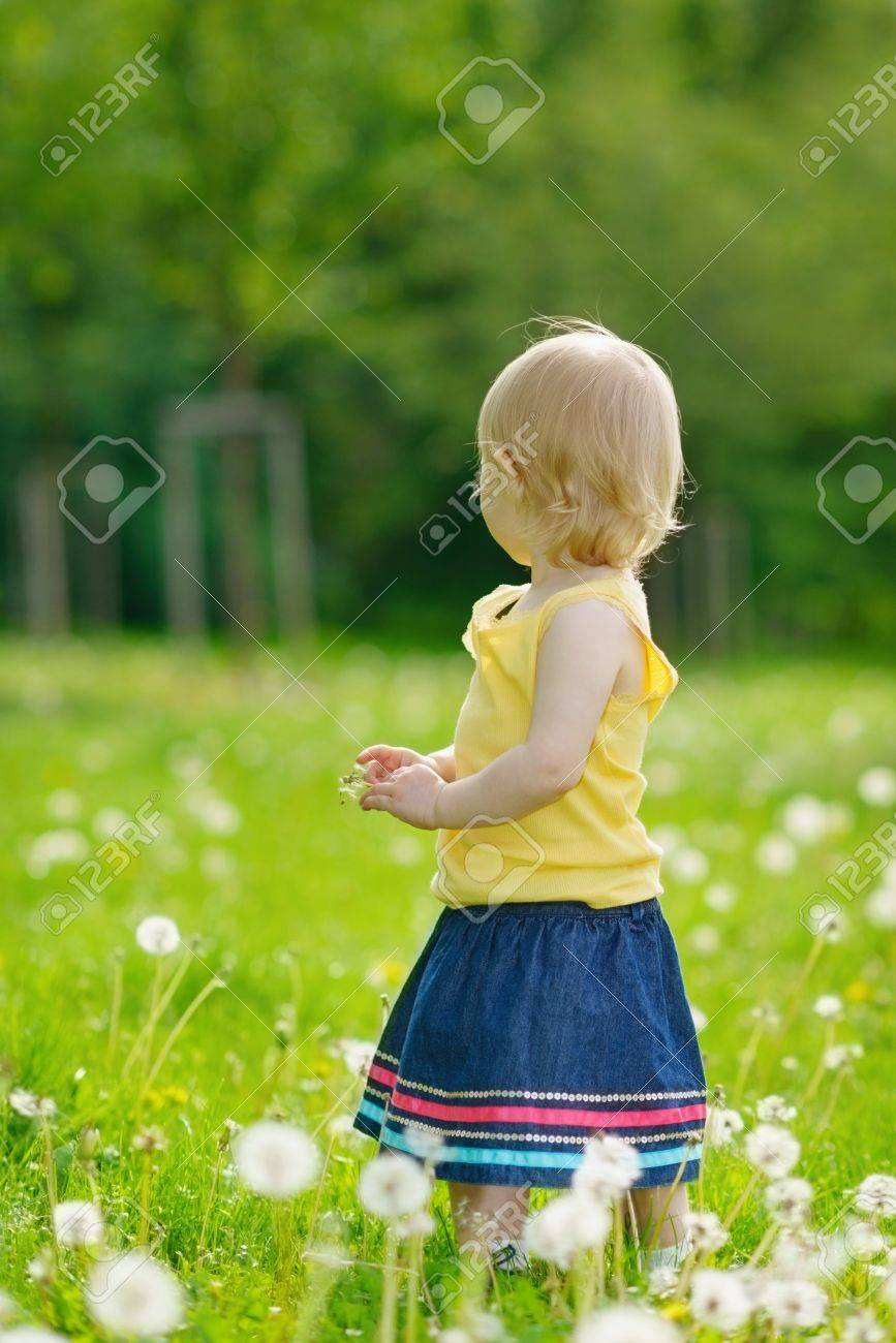 Baby girl on dandelions field looking back Stock Photo - 14003196