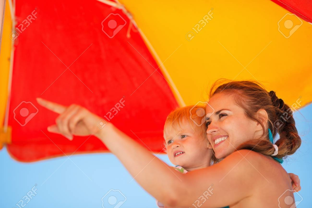Mother showing something baby on beach Stock Photo - 14246460