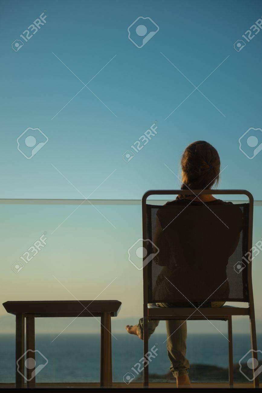 Woman enjoying sunset sitting on balcony. Rear view Stock Photo - 14329463