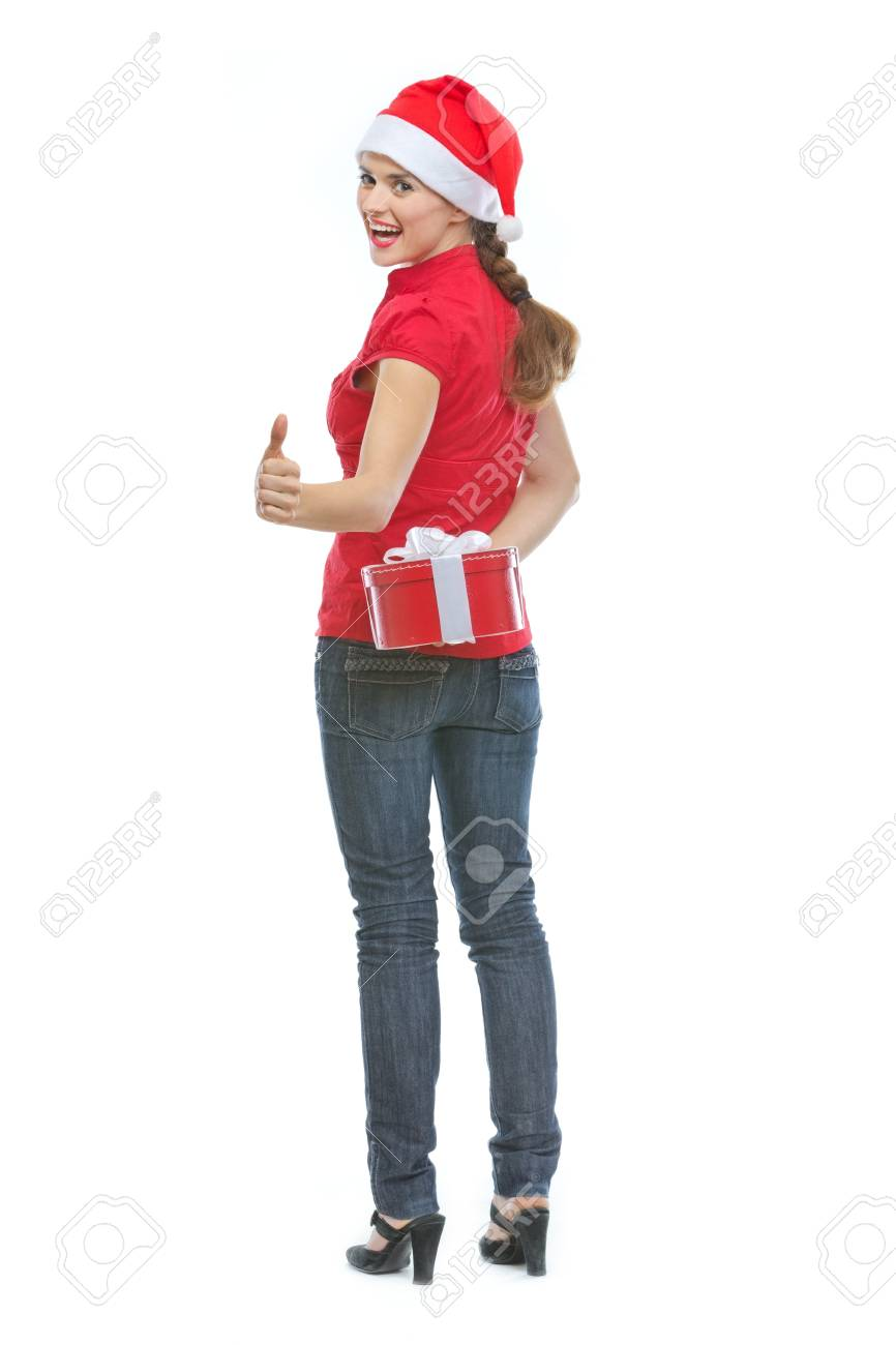 Happy young woman hiding Christmas present box behind back and showing thumbs up Stock Photo - 14768146