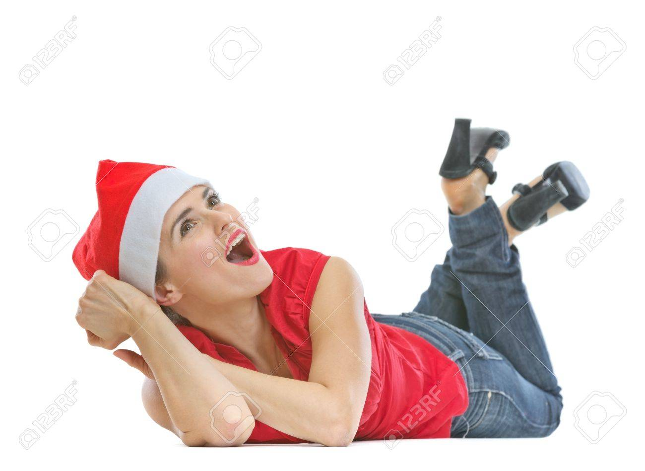 Happy woman in Christmas hat laying on floor and looking on copy space Stock Photo - 20310944