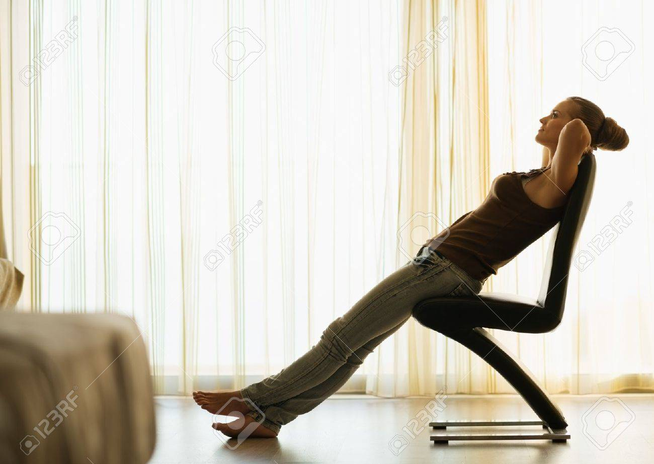 Young Female Relaxing On Modern Chair Near Window Stock Photo