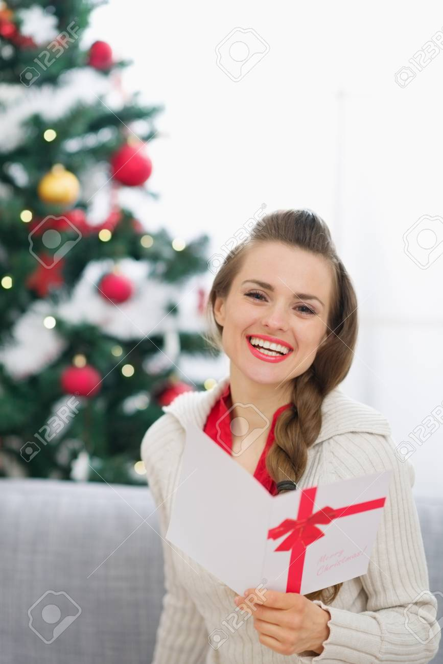 Smiling young woman with Christmas postcard Stock Photo - 15015055