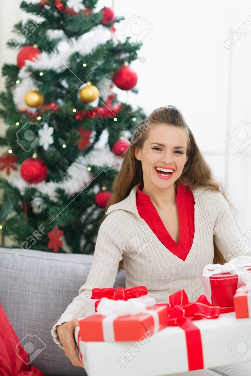 Portrait of smiling young woman near Christmas tree with present boxes Stock Photo - 15015208