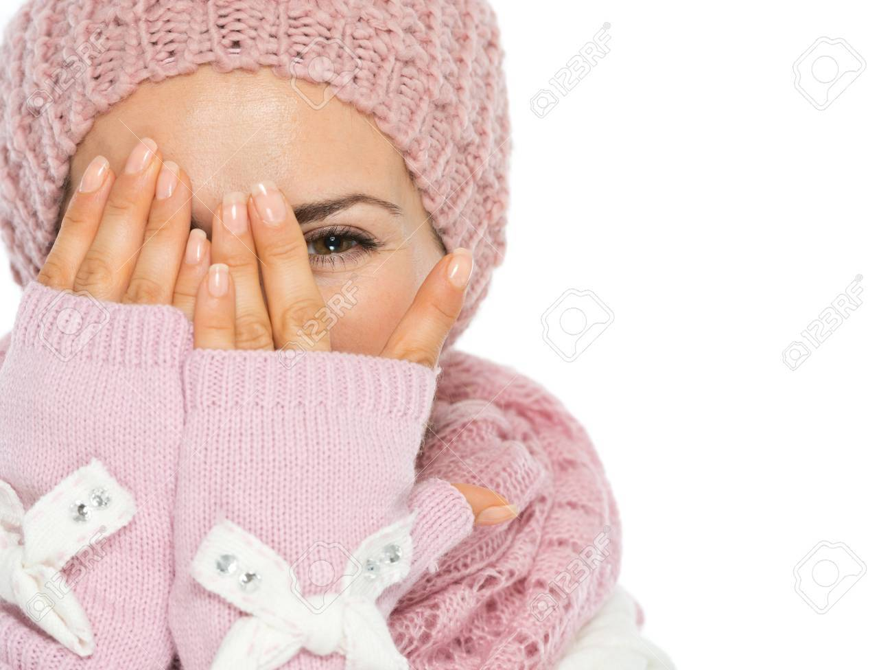 Woman in knit scarf, hat and mittens hiding behind hands Stock Photo - 15892894