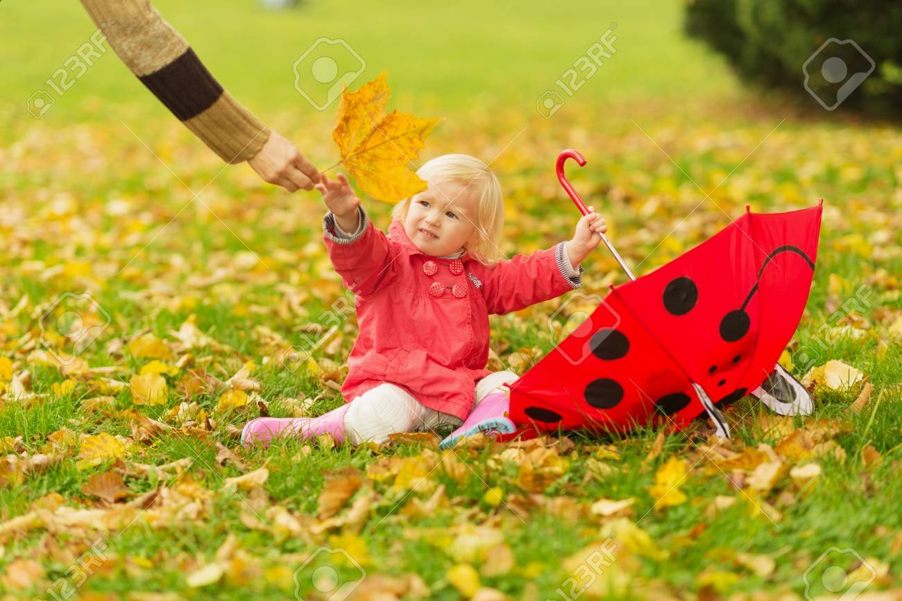 Mother giving baby fallen leave Stock Photo - 16084849