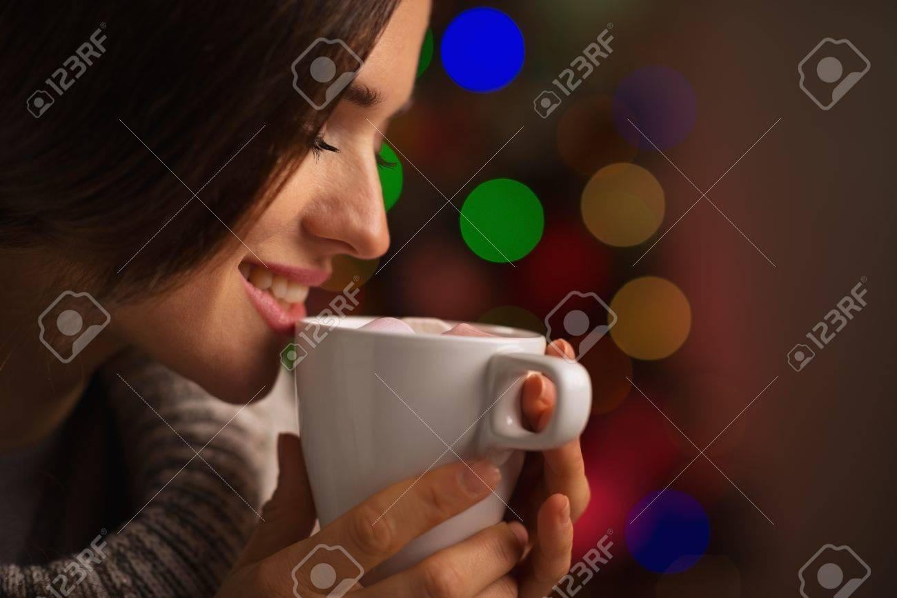 Happy young woman enjoying cup of hot beverage in front of Christmas lights Stock Photo - 16192408