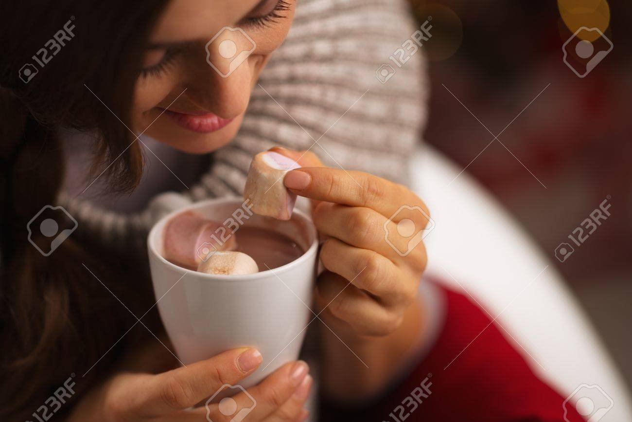 Closeup on woman taking out marshmallow from cup of hot chocolate Stock Photo - 16192421