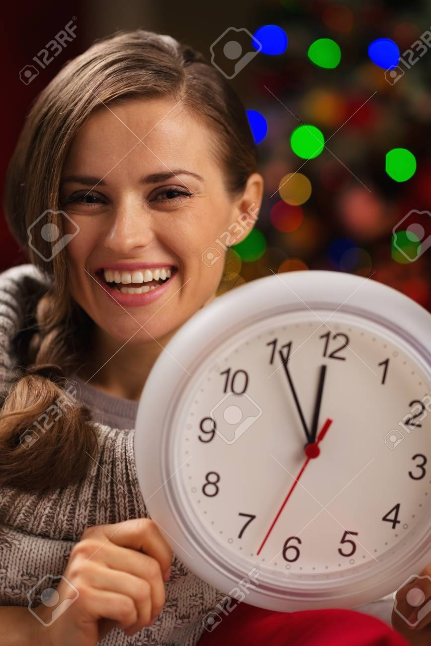 Portrait of smiling woman showing clock in front of Christmas lights Stock Photo - 16192534