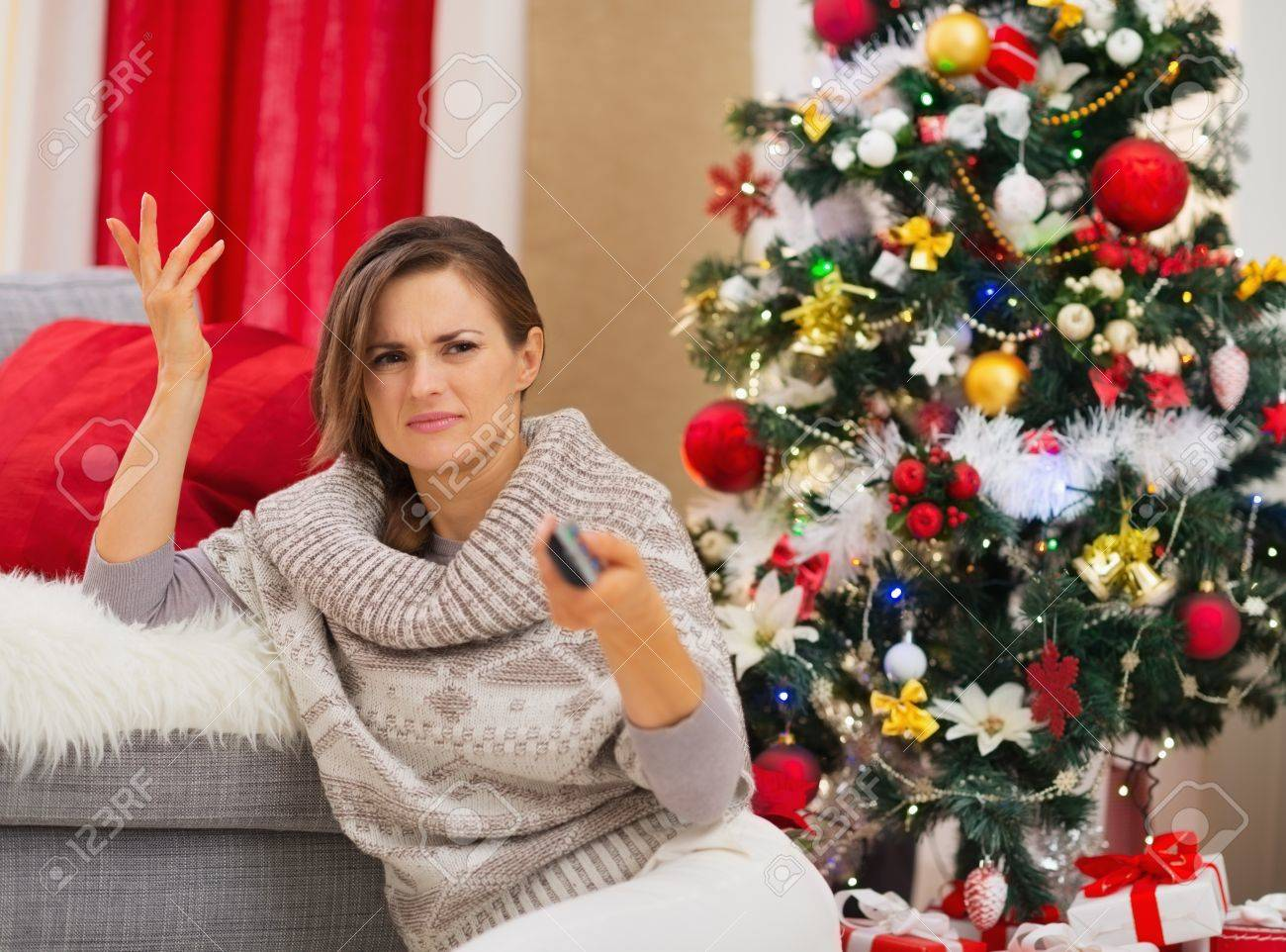 Frustrated woman with TV remote control near Christmas tree Stock Photo - 16467209