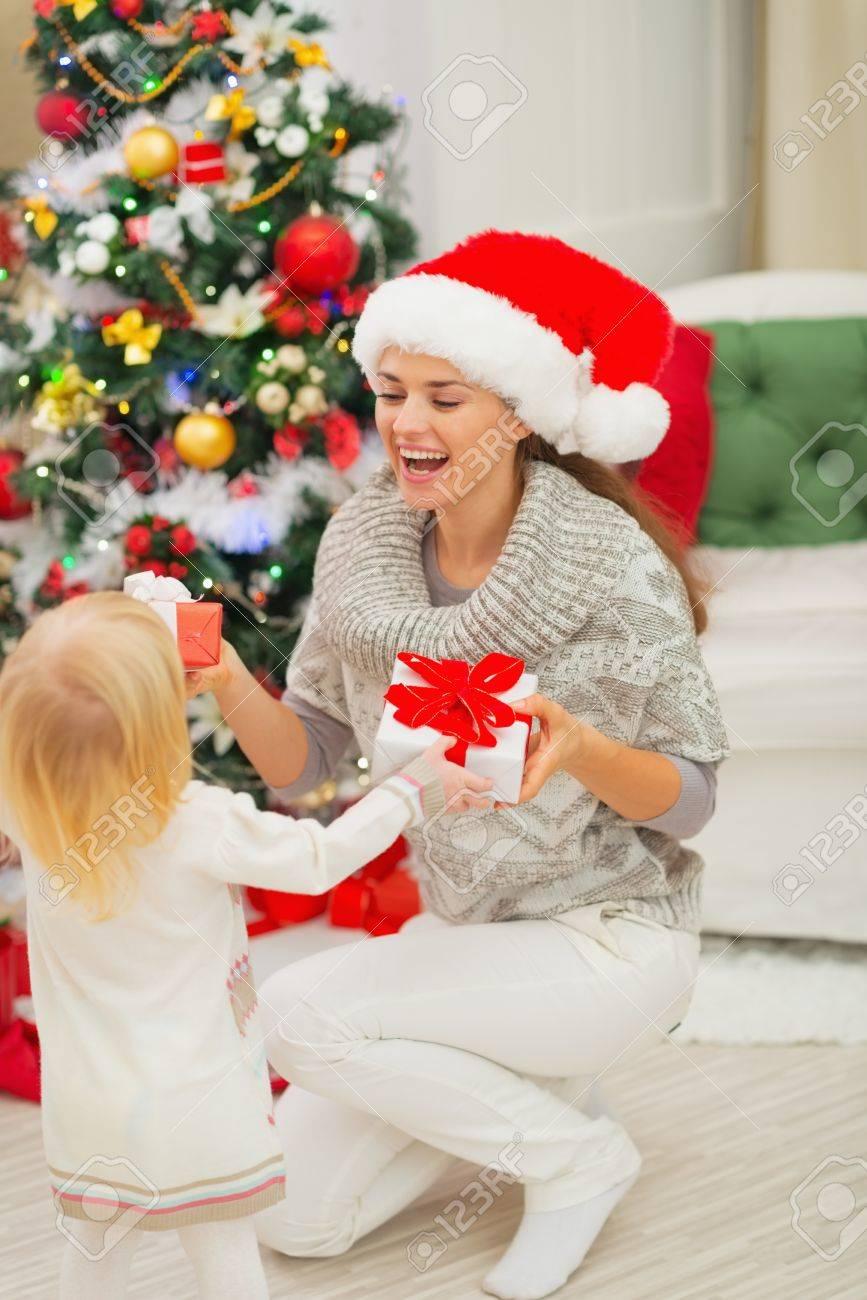 mom and baby girl changing christmas presents stock photo 16578006