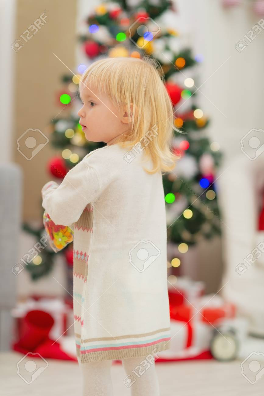 Baby in front of Christmas tree. Rear view Stock Photo - 16577956