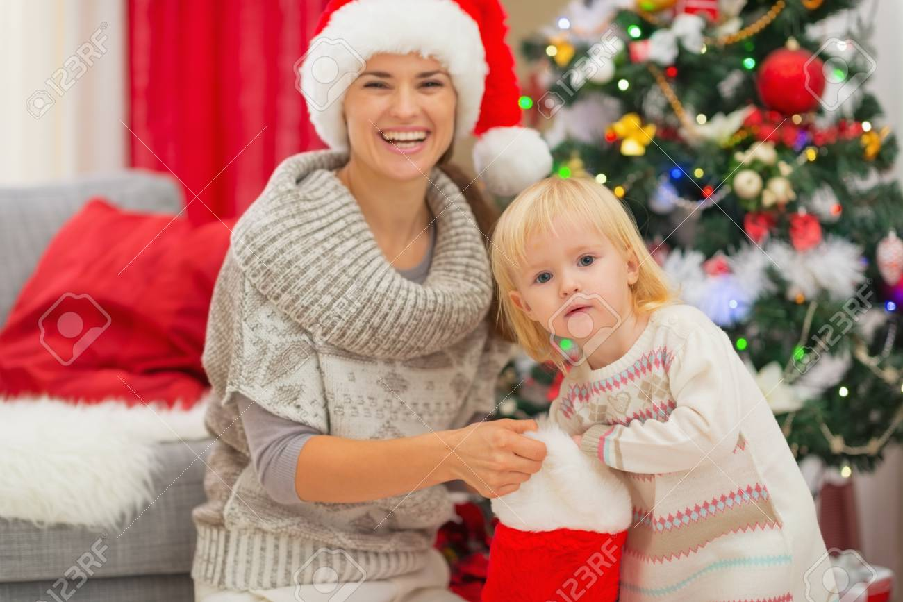 Baby girl taking out present from Christmas sock Stock Photo - 16578013