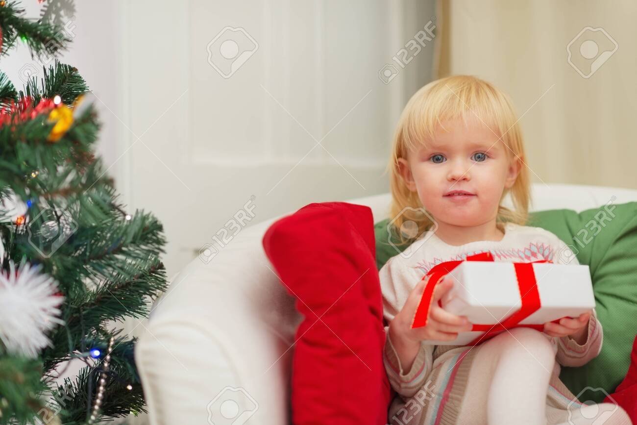 Portrait of baby sitting on chair with Christmas present box Stock Photo - 16577974