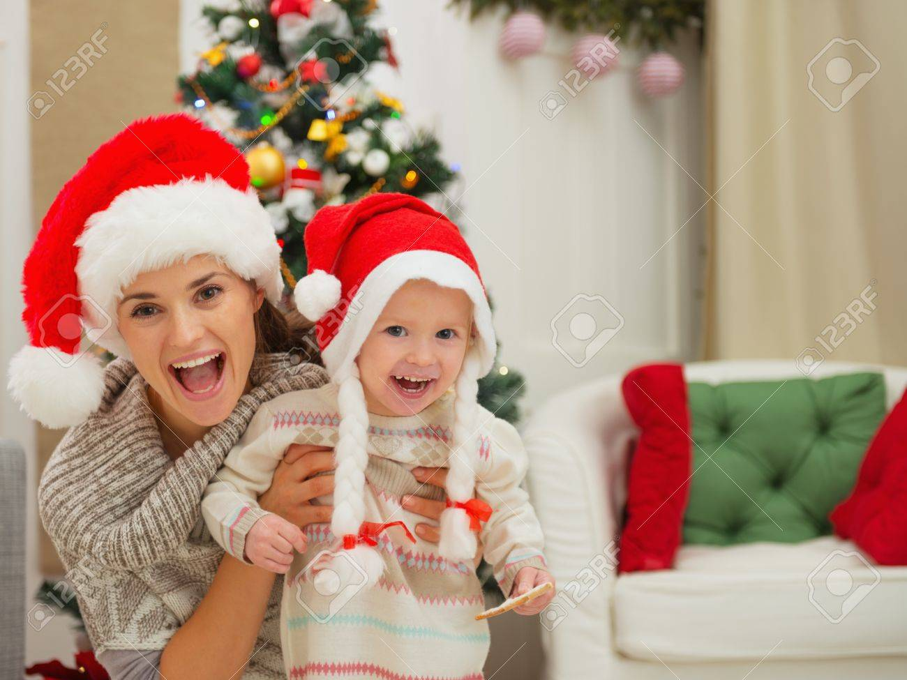 Portrait of mom and eat smeared baby girl in Christmas hats near Christmas tree Stock Photo - 16577988