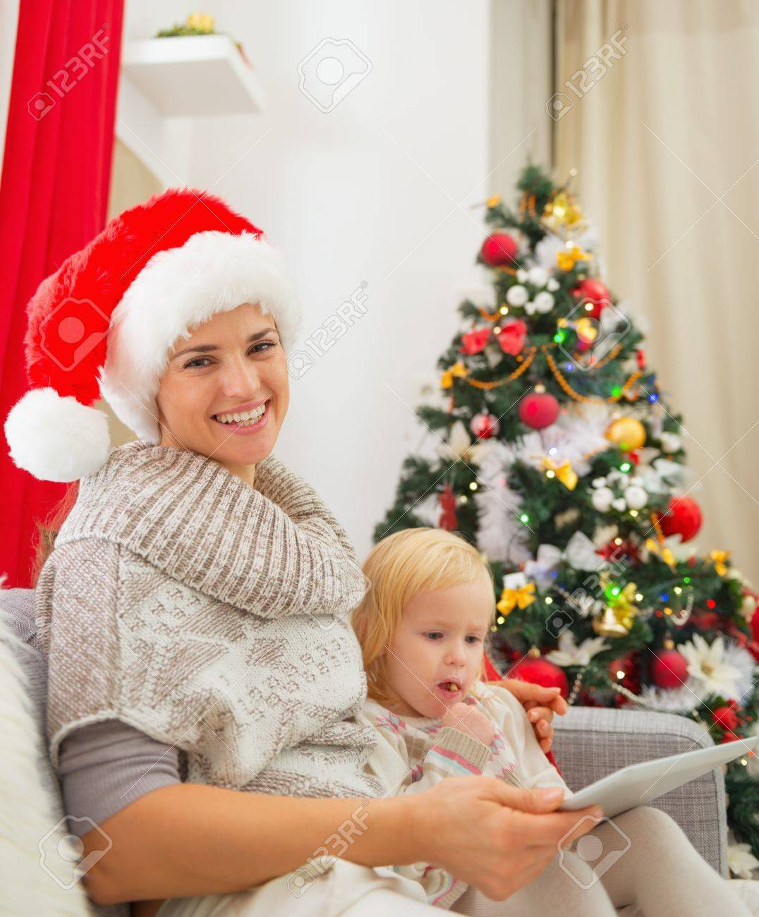 Smiling mother and baby girl using tablet PC near Christmas tree Stock Photo - 16577965