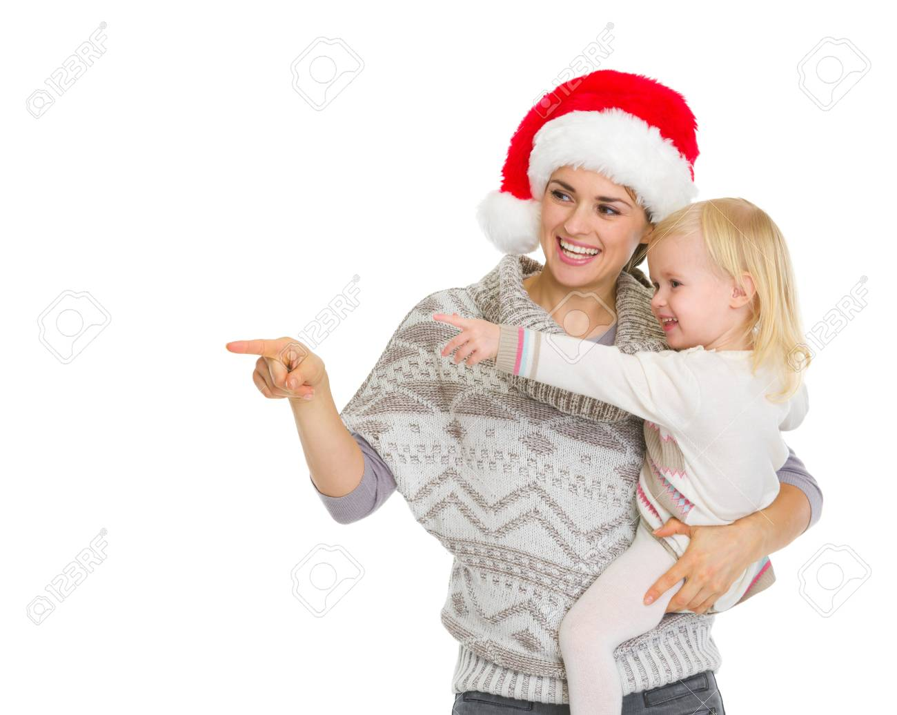 Happy mother in Christmas hat and baby girl pointing on copy space Stock Photo - 16577944
