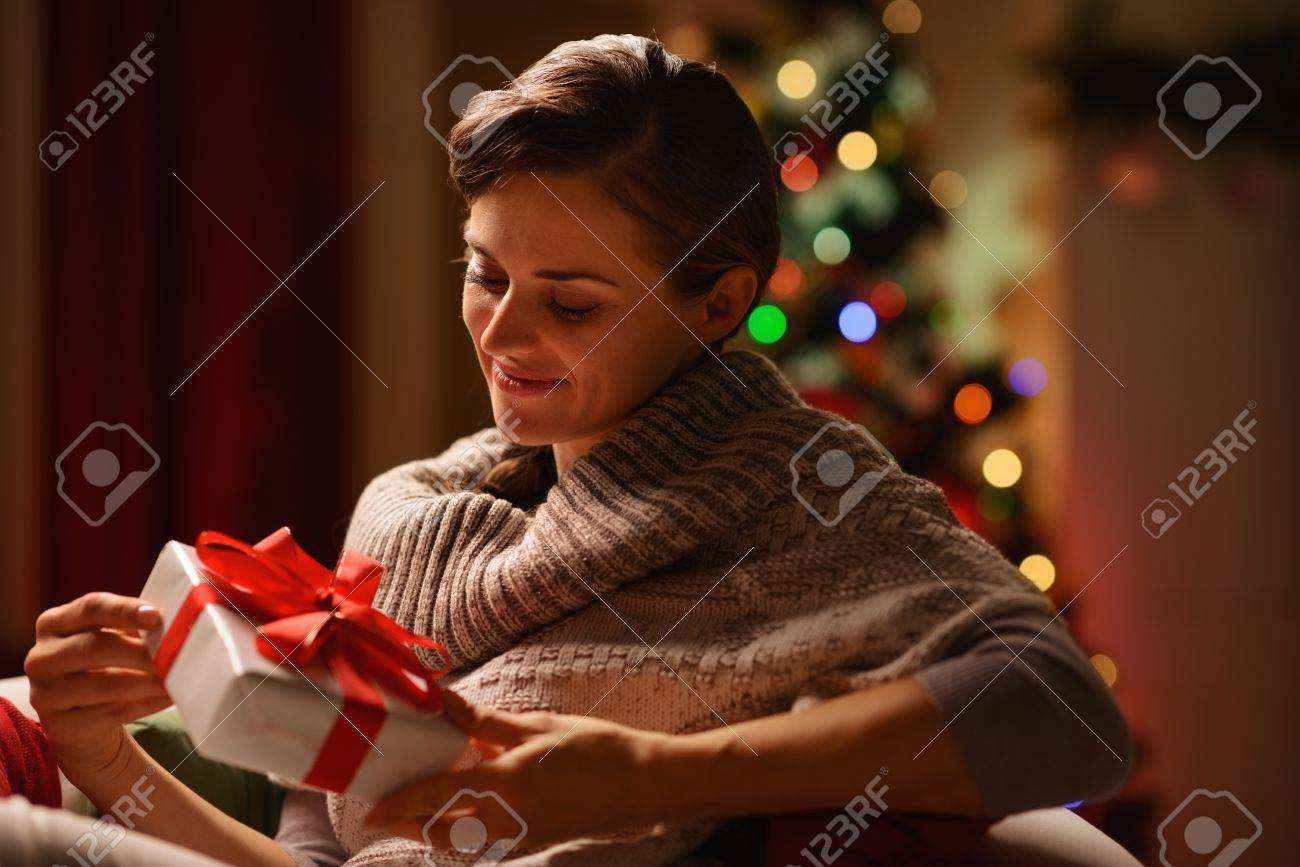 Happy young woman sitting chair with Christmas present box Stock Photo - 16711021