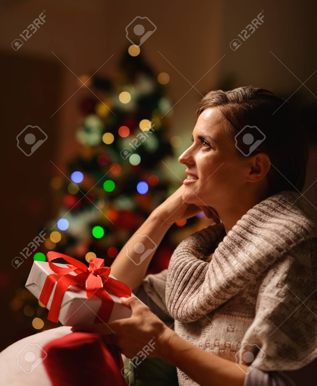 Dreaming young woman sitting chair with Christmas present box Stock Photo - 16711016