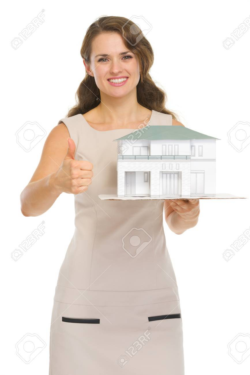 Happy woman landlord with scale model of house showing thumbs up Stock Photo - 16882345