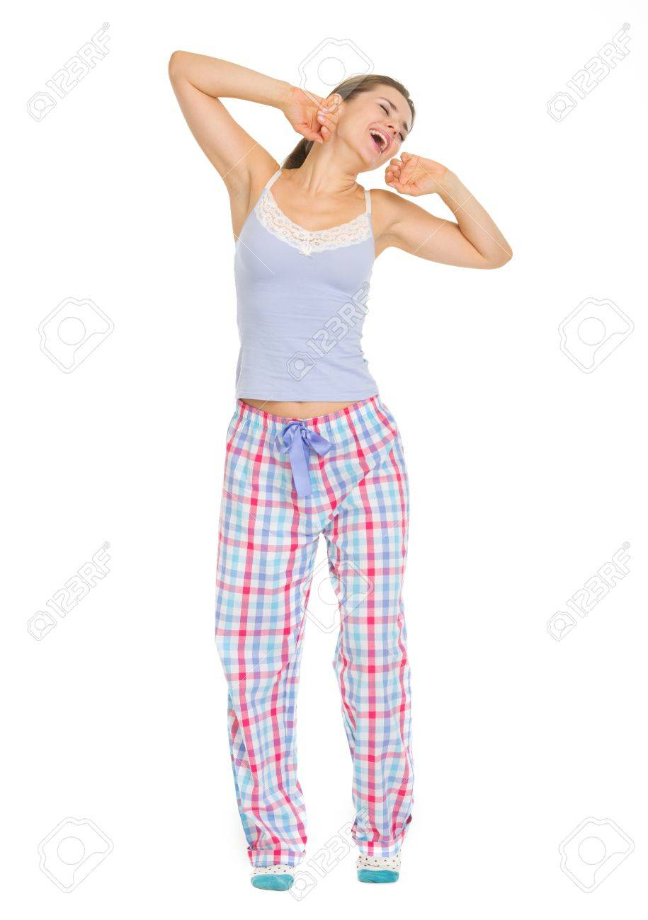 Full length portrait of young woman in pajamas stretching and yawing Stock Photo - 17137449