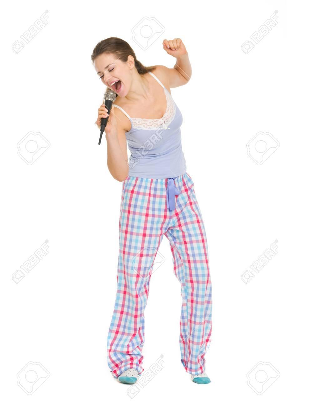 80f4d631243 Foto de archivo - Retrato de cuerpo entero de una mujer joven en pijama  cantando en micrófono