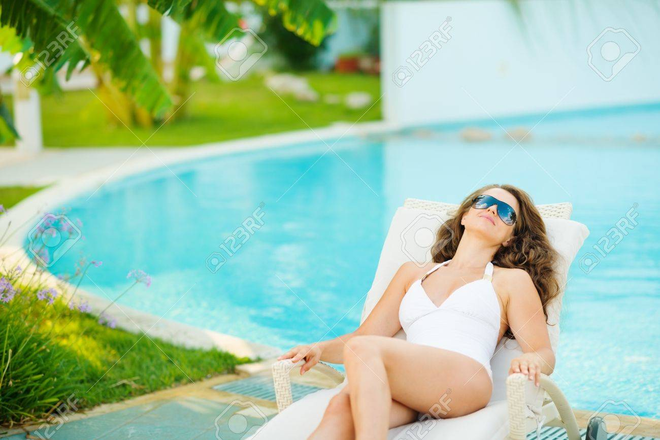 Young woman in swimsuit relaxing poolside Stock Photo - 17283143