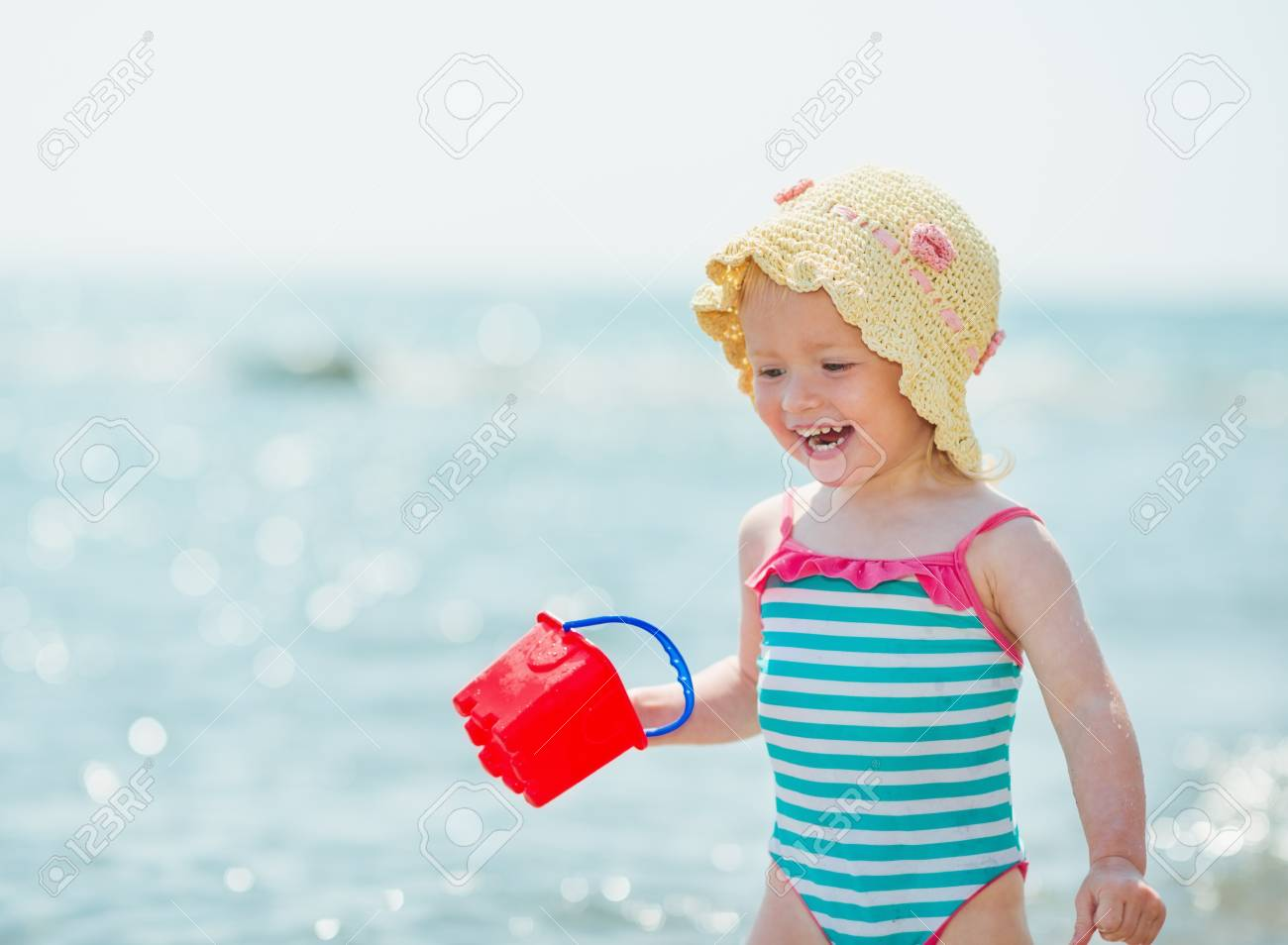Smiling baby playing with pail on seashore Stock Photo - 17283116