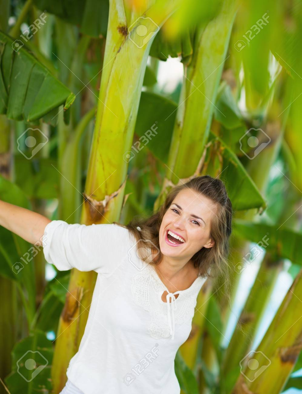 Laughing young woman among tropical palms Stock Photo - 17283113