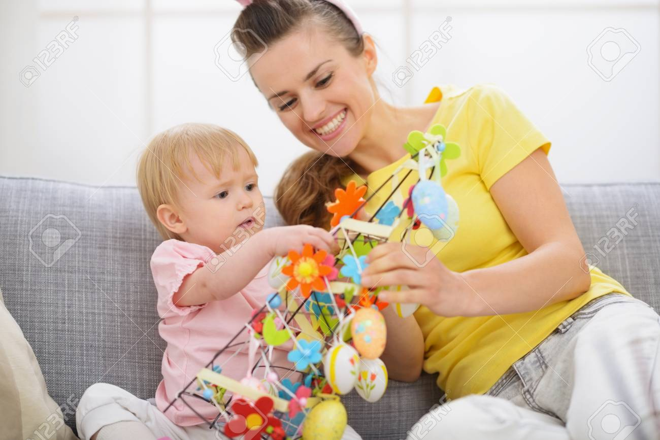 Happy mother and baby making Easter decoration Stock Photo - 17304828