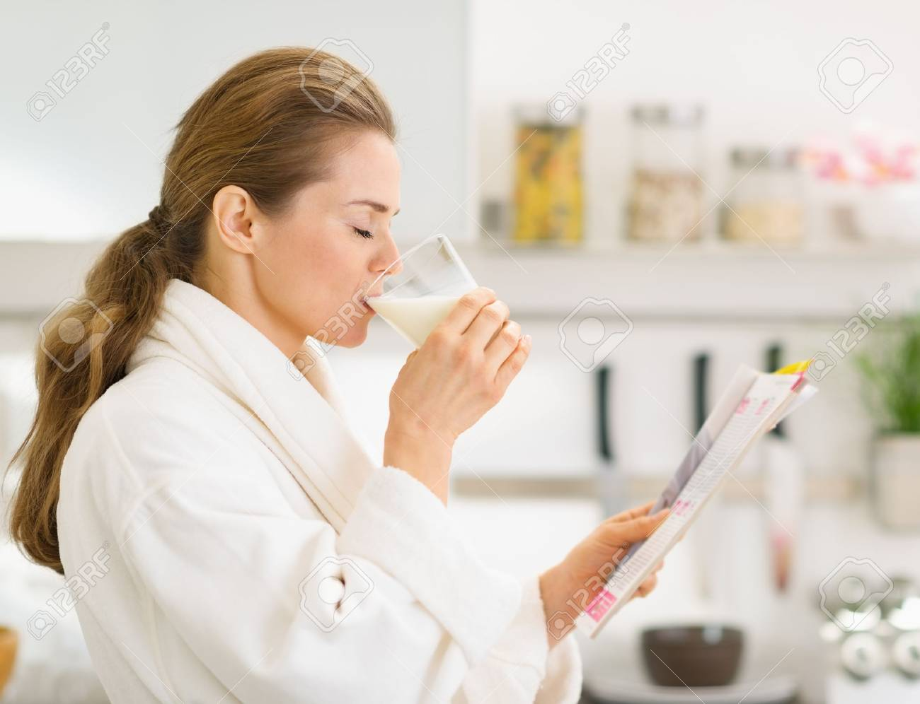 Young woman in bathrobe with magazine and drinking milk Stock Photo - 17800081