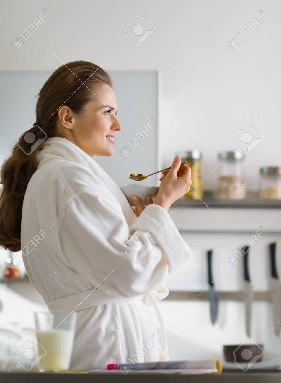 Young woman in bathrobe eating breakfast in morning Stock Photo - 17800082