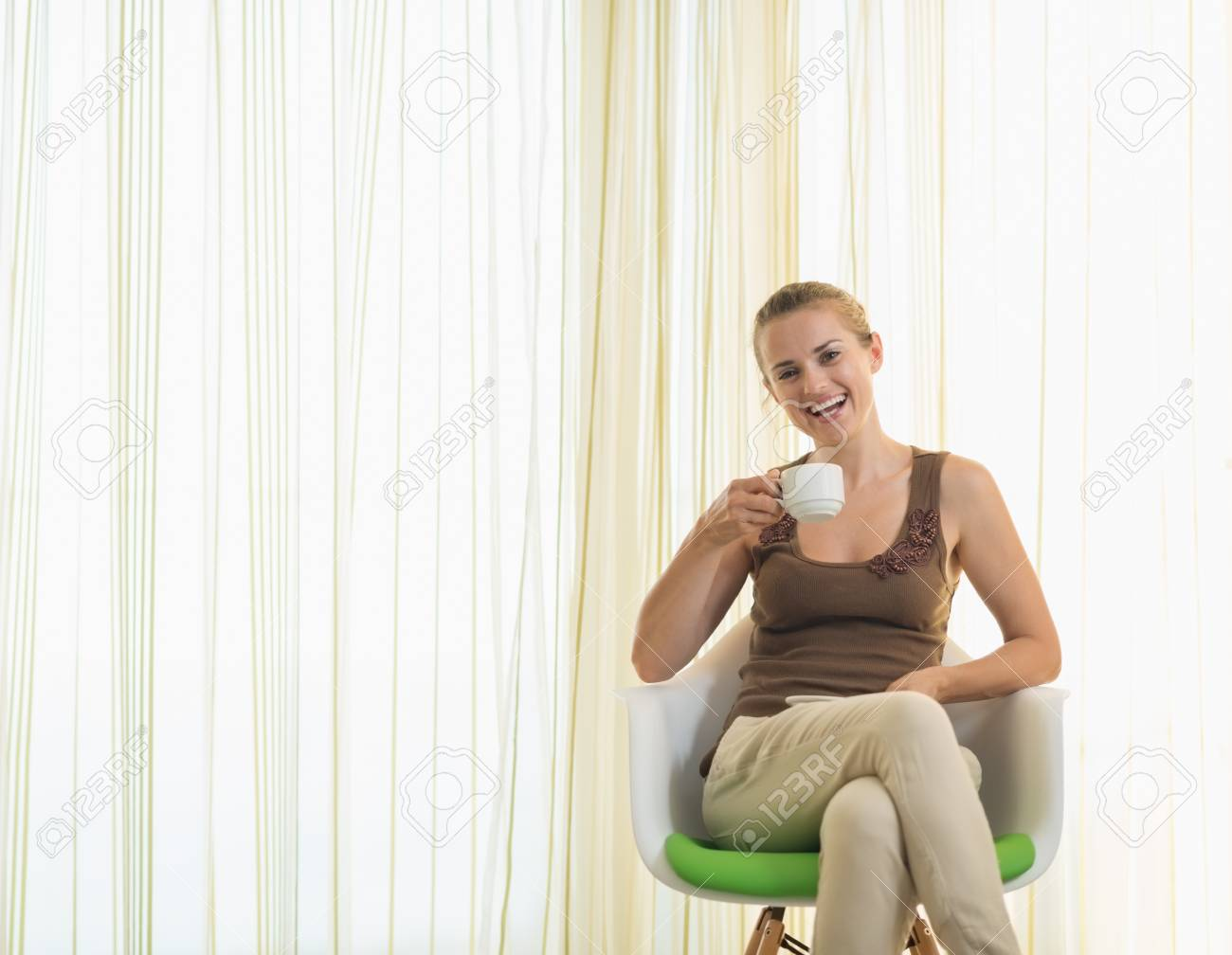 Happy young woman drinking tea in modern chair Stock Photo - 17926416