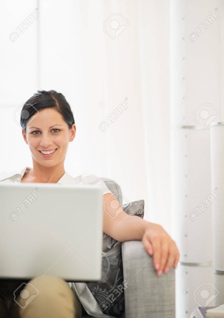 Smiling young woman using laptop Stock Photo - 18493216