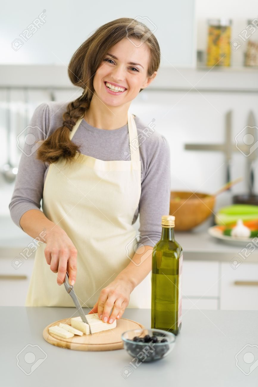 Smiling young housewife cutting fresh cheese Stock Photo - 19093530