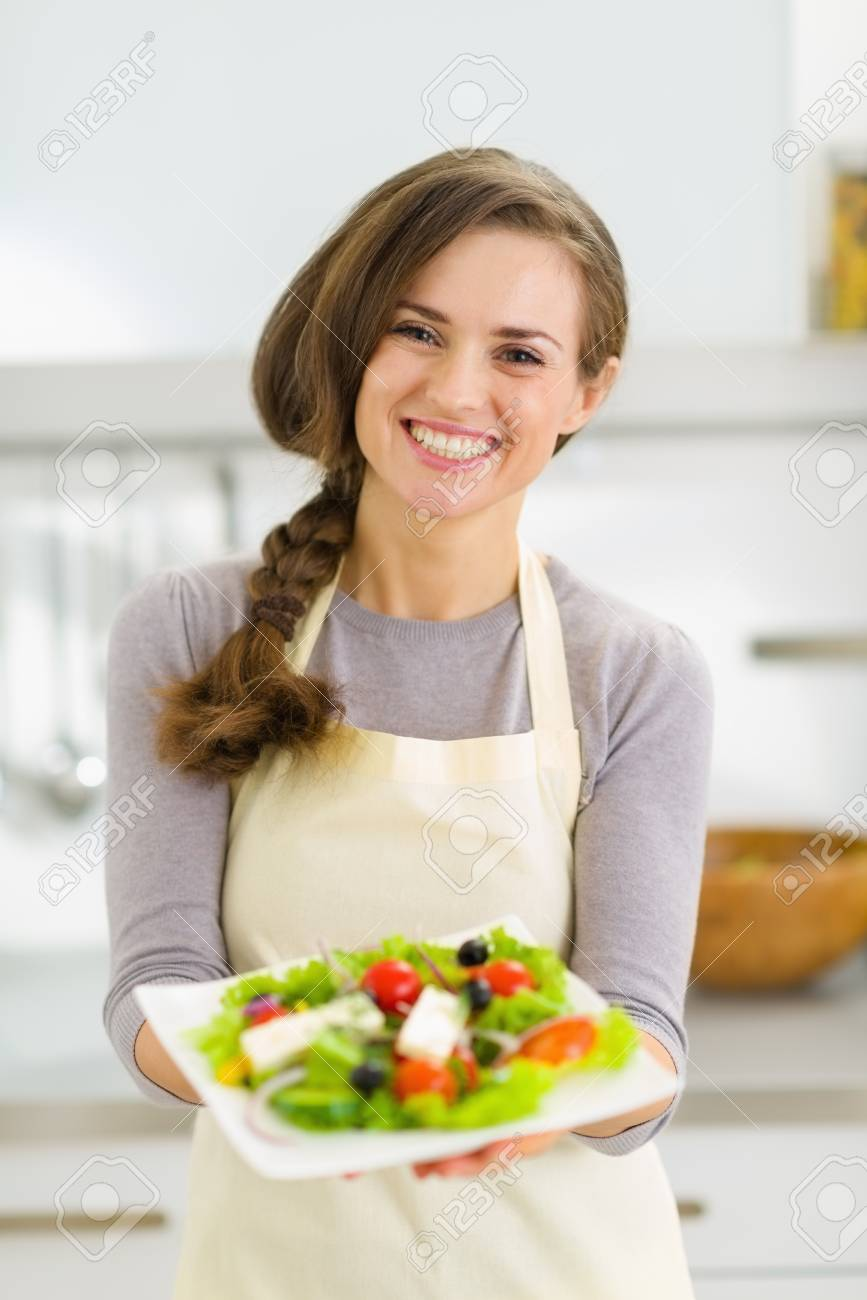 Happy young housewife giving fresh salad Stock Photo - 19093504