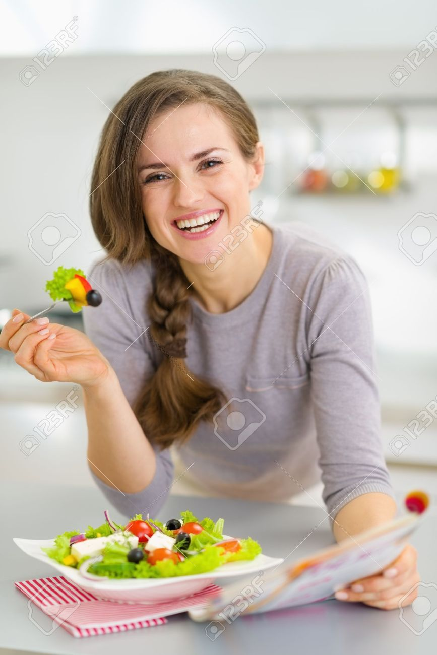 Smiling young housewife eating fresh salad and reading magazine in kitchen Stock Photo - 19093478