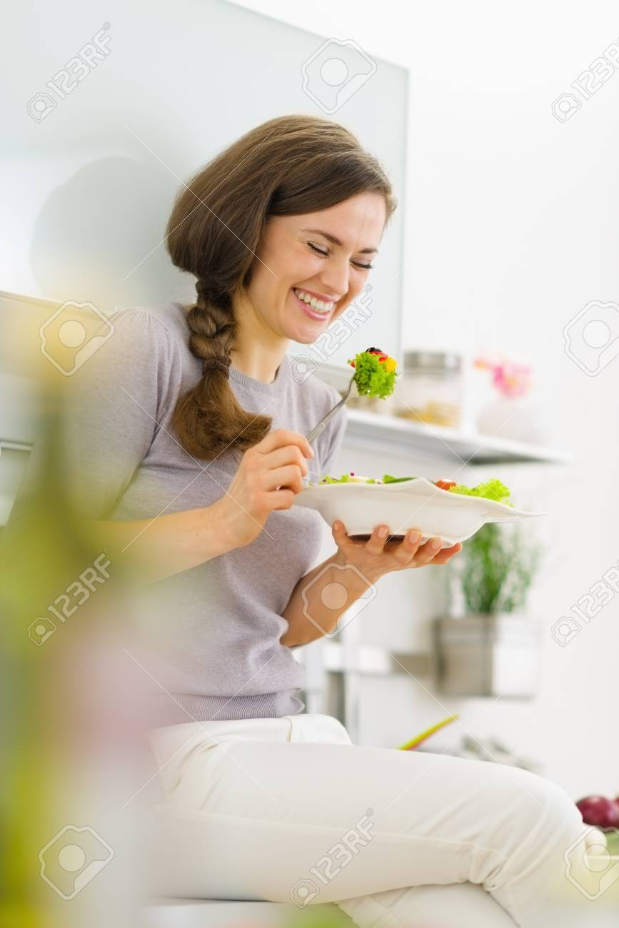 Happy young woman eating fresh salad in modern kitchen Stock Photo - 19093440