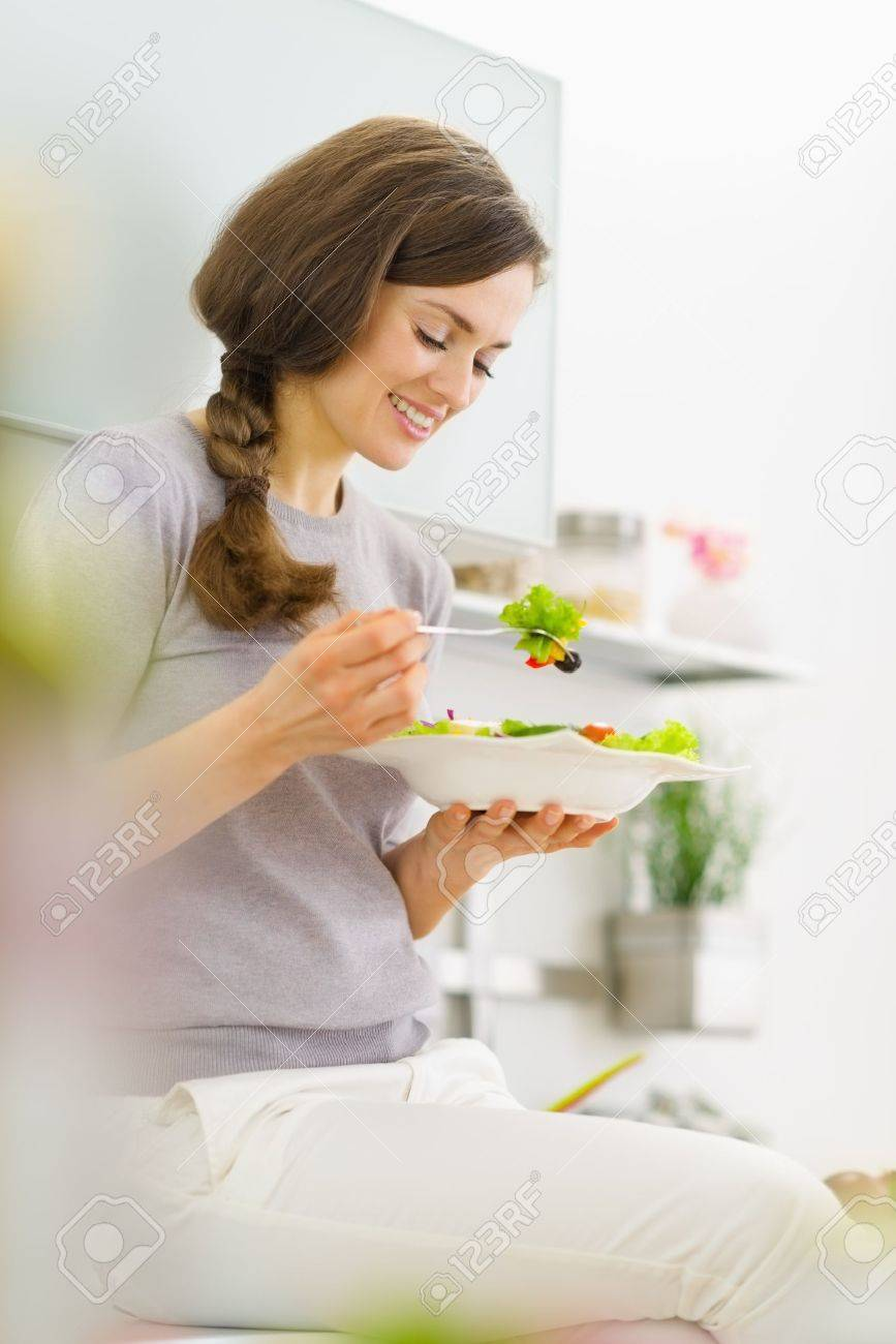 Young woman eating fresh salad in modern kitchen Stock Photo - 19093516