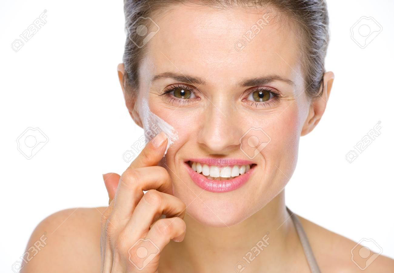 Beauty portrait of happy young woman applying creme on cheek Stock Photo - 19848815
