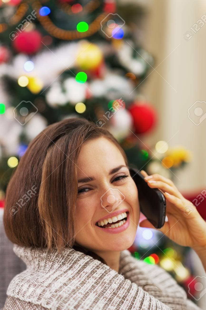 Happy young woman talking cell phone near christmas tree Stock Photo - 21353906