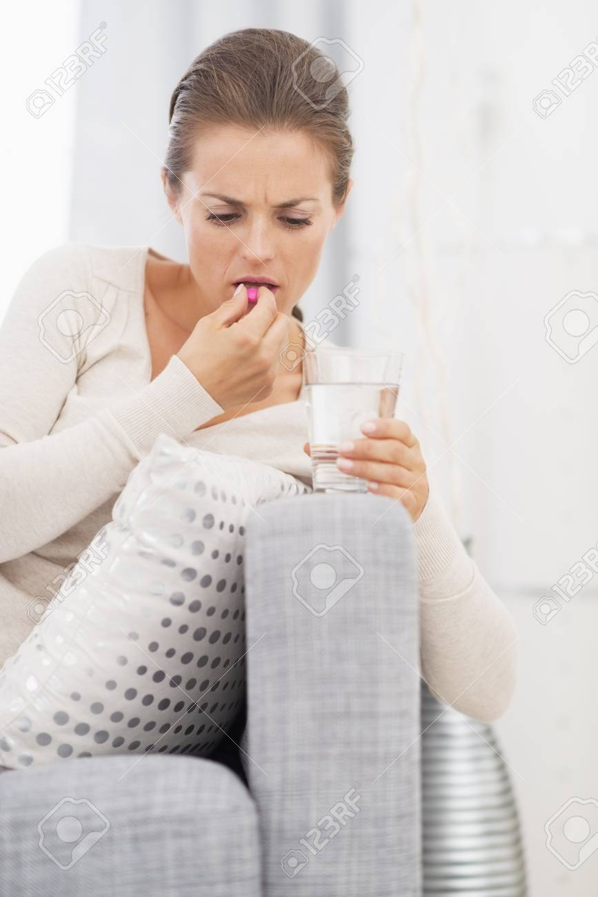 Young woman eating pill Stock Photo - 21359727