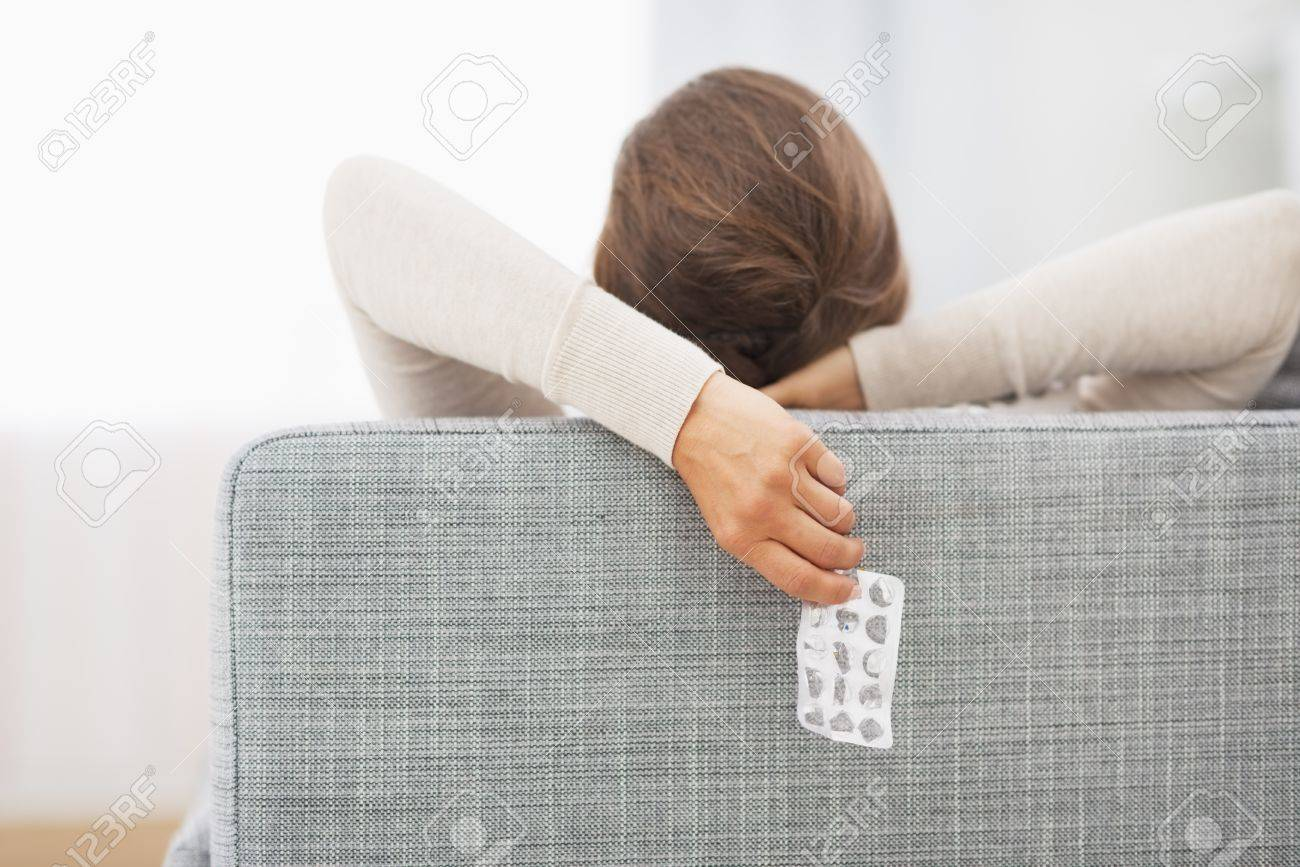 Closeup on empty medicine blister package in hand of young woman laying on sofa Stock Photo - 21341850