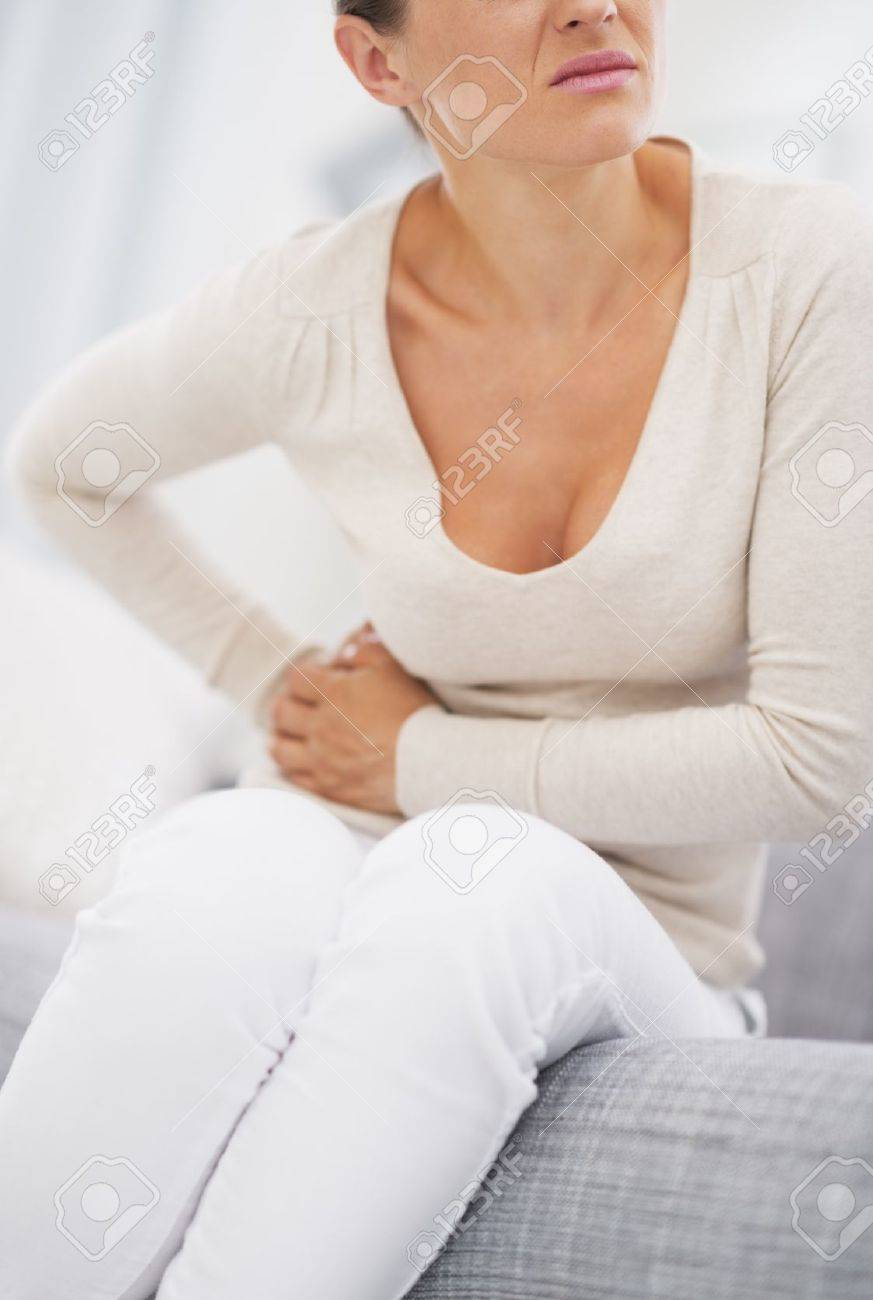 Closeup on young woman having stomach pain Stock Photo - 21359758