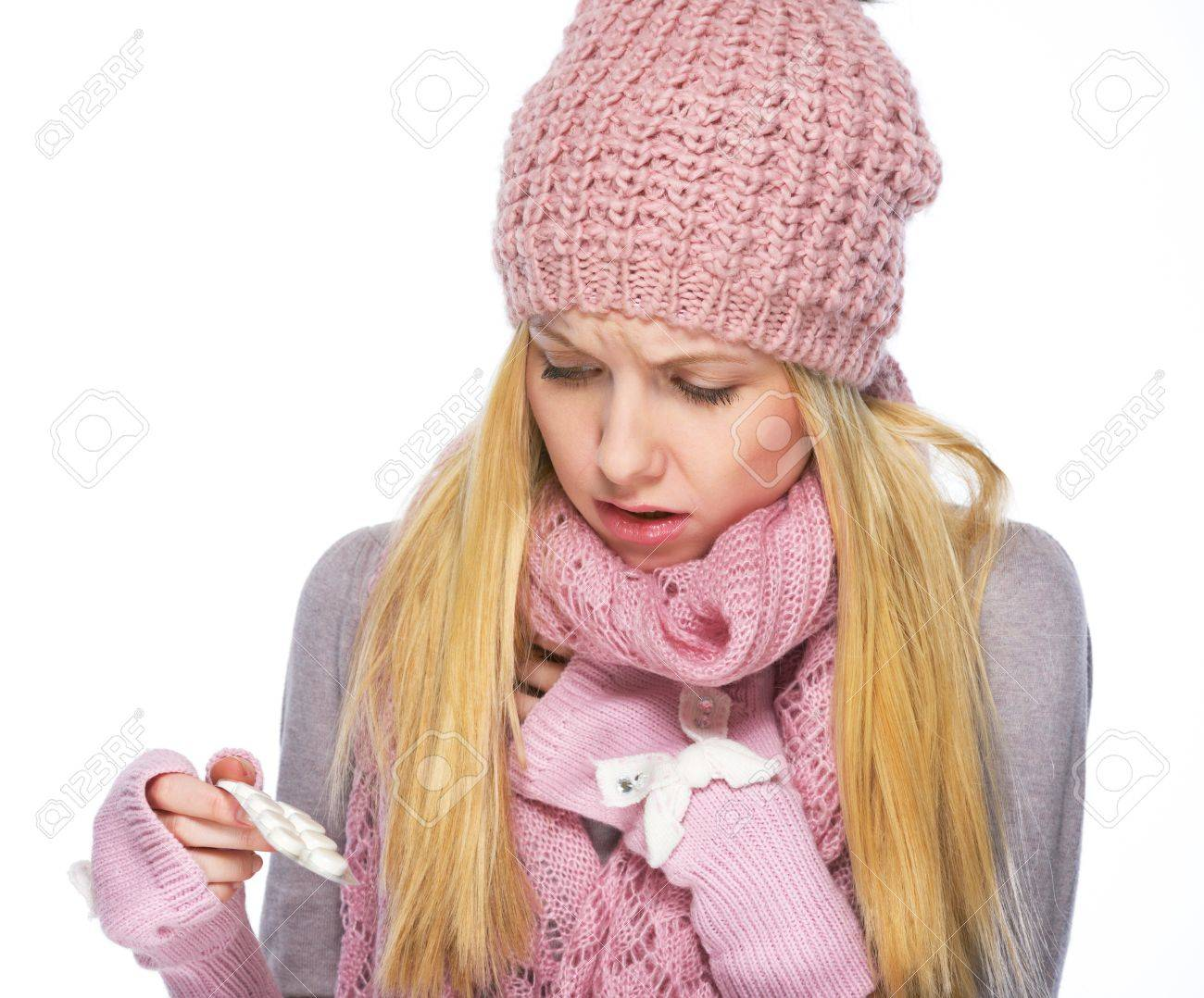 Ill teenager girl in winter hat and scarf looking on pills pack Stock Photo - 21354857