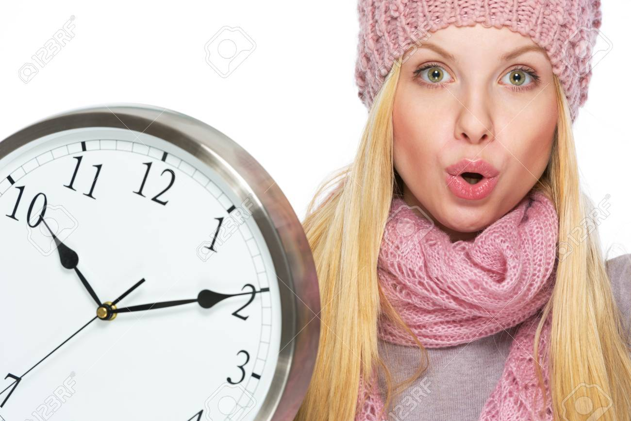 Portrait of surprised teenager girl in winter hat and scarf with clock Stock Photo - 21354867