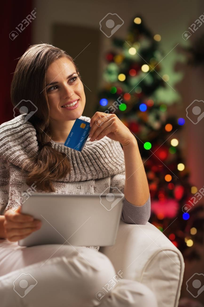Thoughtful young woman with credit card and tablet pc near christmas tree Stock Photo - 21568013