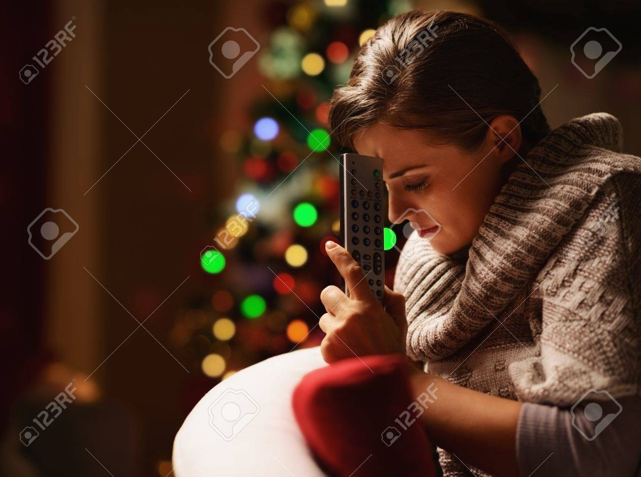 Frustrated young woman with tv remote control in front of christmas tree Stock Photo - 21568200